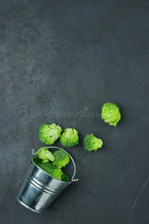Segmentos dos brócolis do verde do Placer de uma cubeta pequena Teste padrão saudável comer no fundo escuro Copie a opinião super fotografia de stock