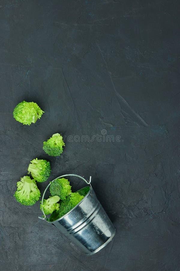 Segmentos dos brócolis do verde do Placer de uma cubeta pequena Teste padrão saudável comer no fundo escuro Copie a opinião super imagens de stock royalty free