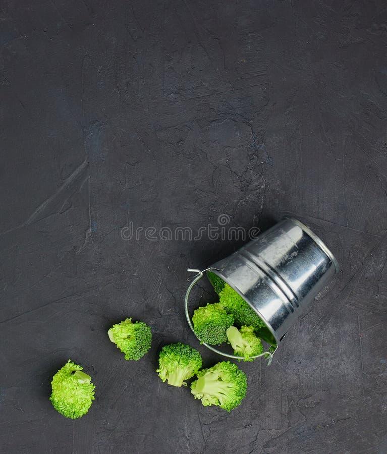 Segmentos dos brócolis do verde do Placer de uma cubeta pequena Teste padrão saudável comer no fundo escuro Copie a opinião super imagens de stock