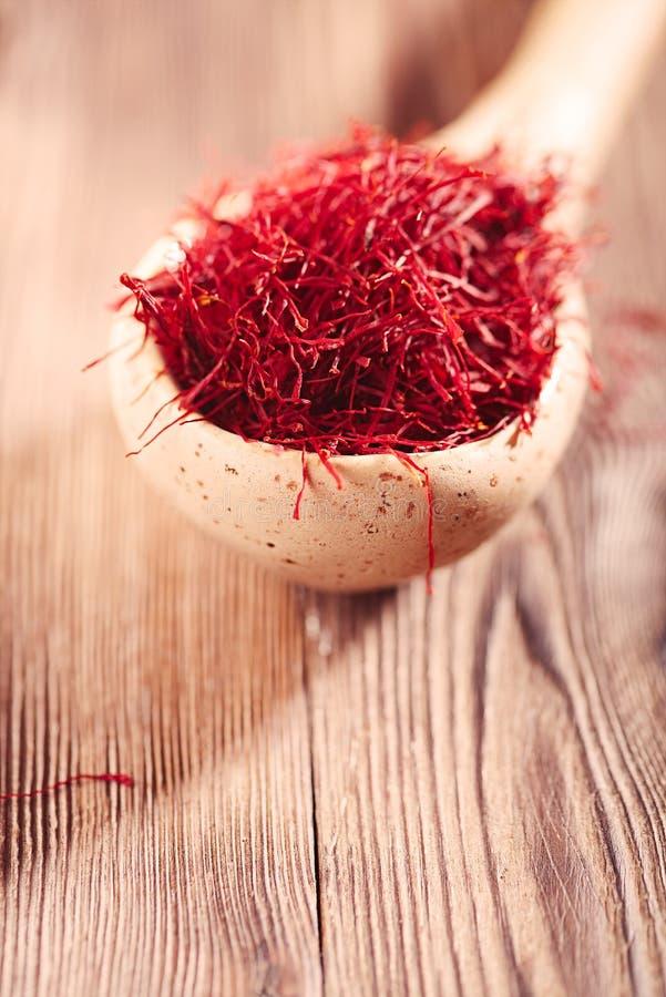 Segmentos Saffron com colheres-medida fotografia de stock royalty free