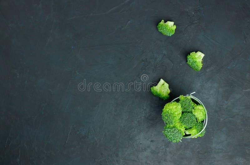 Segmentos verdes dos brócolis em uma cubeta pequena Teste padrão saudável comer no fundo escuro Copie a opinião superior do espaç imagem de stock