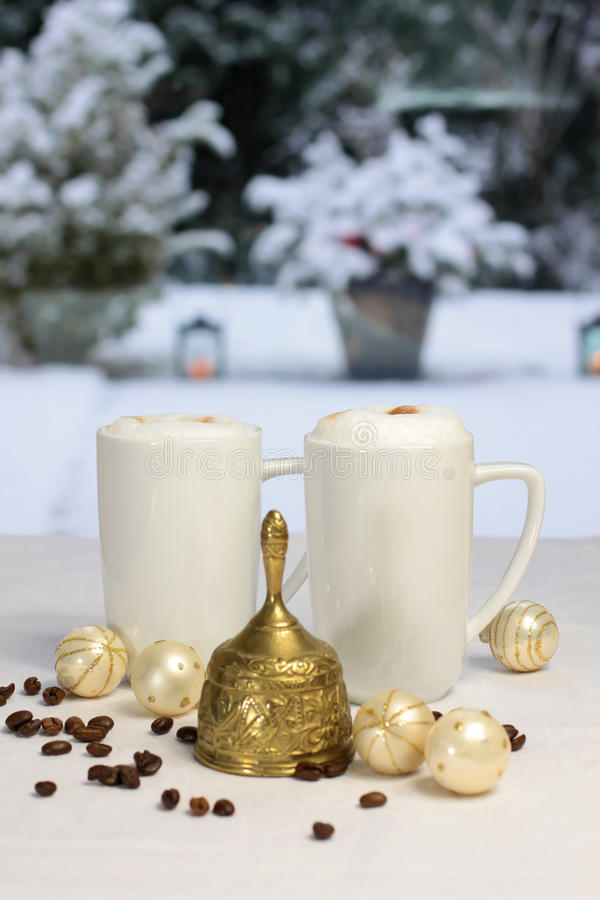 Segnalatore acustico di natale e tazze di caffè dorati fotografia stock