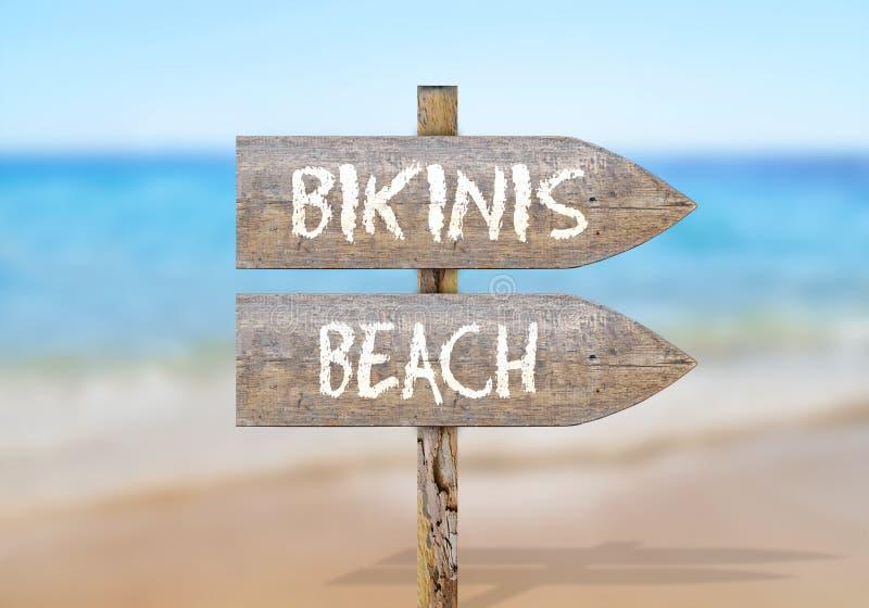 Segnale di direzione di legno con la spiaggia dei bikini fotografia stock libera da diritti