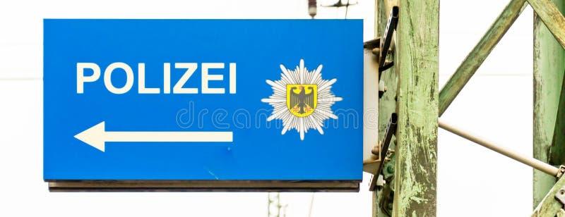Segnale di informazione per il commissariato di polizia seguente con una freccia bianca su una terra blu e sulla stemma della Rep fotografie stock