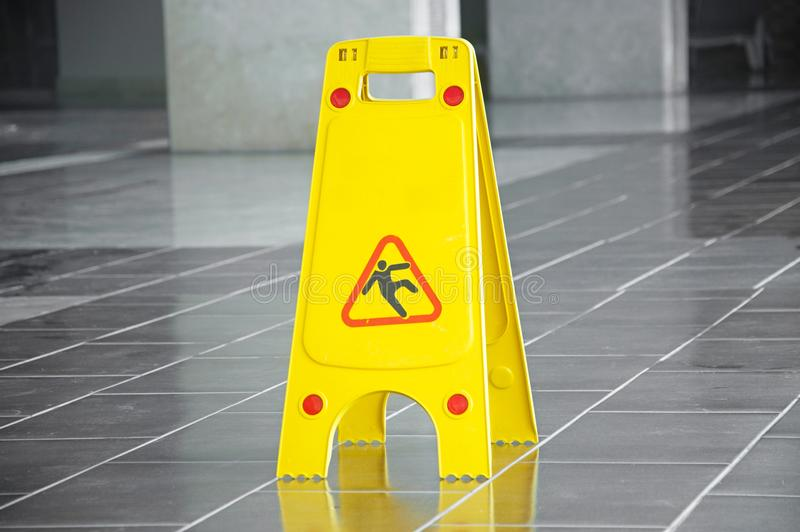 Segnale di pericolo della superficie sdrucciolevole del pavimento e simbolo in costruzione, corridoio fotografie stock