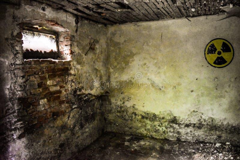 Segnale di pericolo radioattivo sulla parete sporca di lerciume in costruzione abbandonata dalla zona di esclusione Atmosfera di  immagini stock libere da diritti