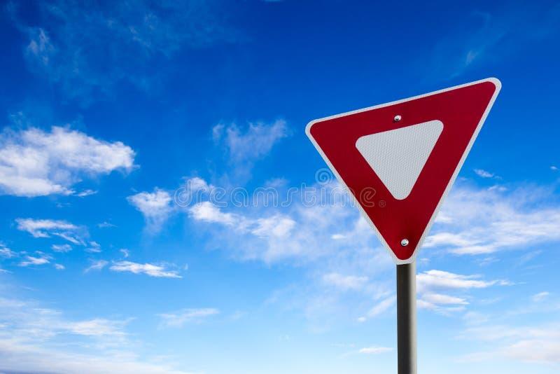 Segnale di precedenza di traffico con il fondo del cielo blu fotografie stock libere da diritti