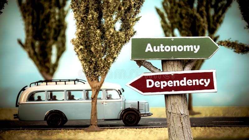 Segnale stradale ad autonomia contro la dipendenza fotografia stock