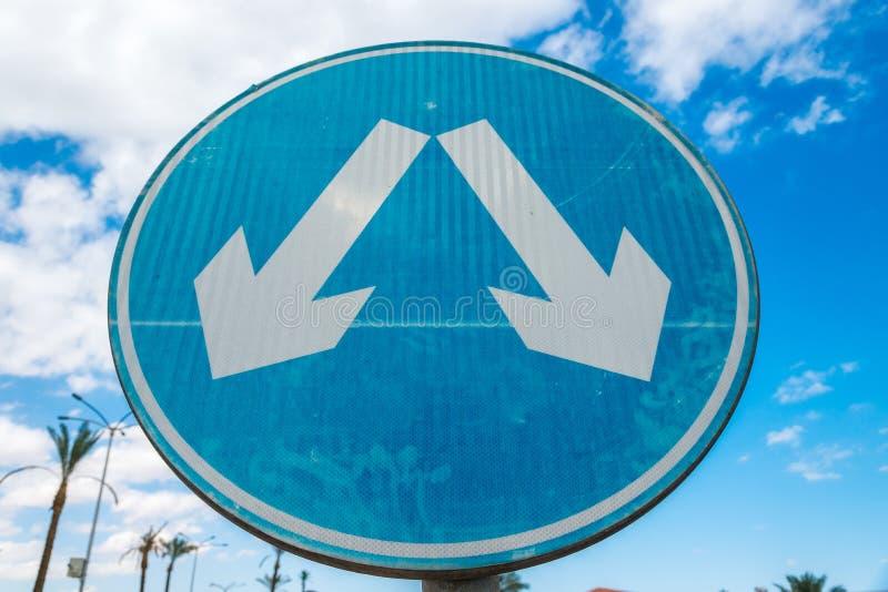 Segnale stradale blu rotondo con le frecce d'avvertimento diagonali bianche Struttura orizzontale fotografie stock