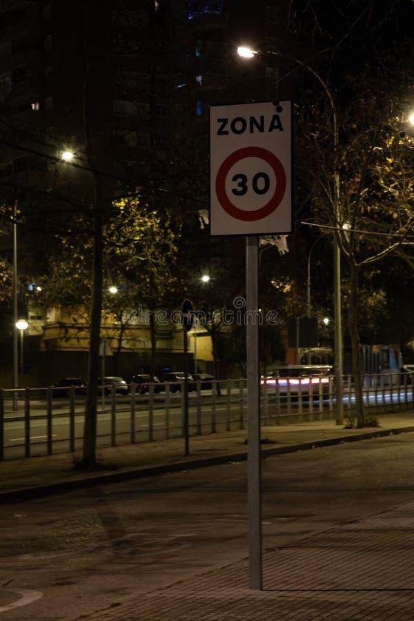 Segnale stradale che indica un limite a bassa velocità di 30 km/h nell'area urbana alla notte fotografia stock
