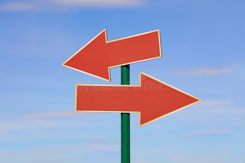 Segnale stradale con due frecce rosse sopra cielo blu immagini stock libere da diritti