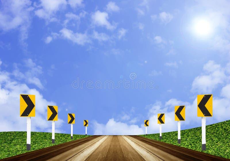 Segnale stradale della freccia e pavimento delle plance di legno su cielo blu immagine stock