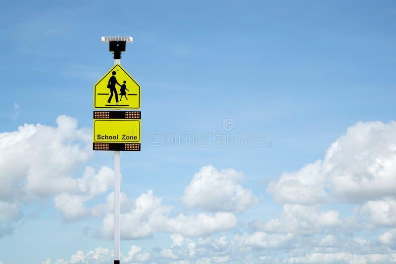 Segnale stradale della scuola con il pannello delle pile solari per i risparmi energetici sopra immagini stock