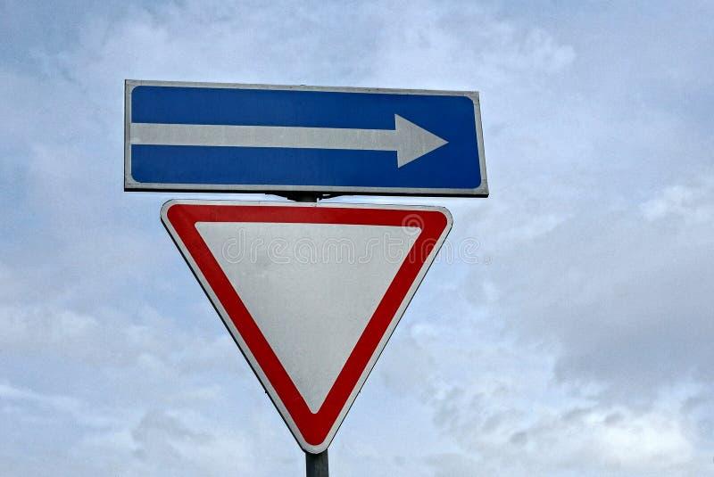 Segnale stradale e freccia triangolari sui precedenti del cielo fotografia stock