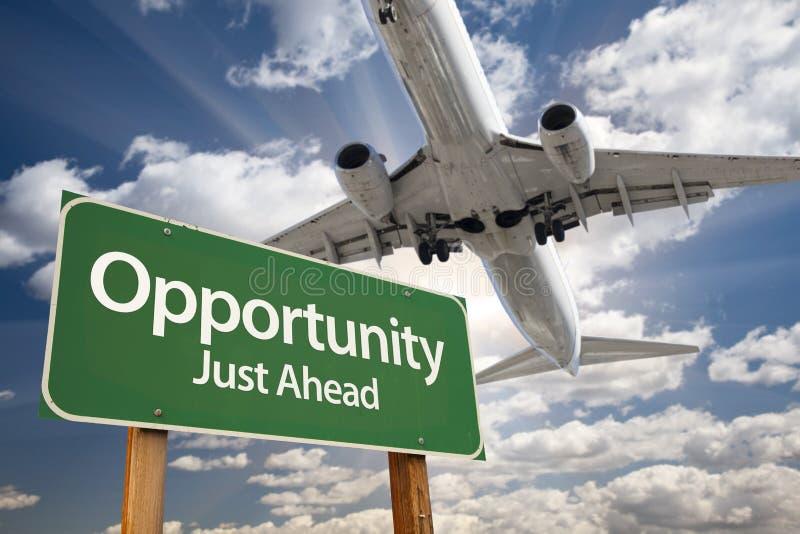 Segnale stradale ed aeroplano verdi di opportunità qui sopra fotografia stock