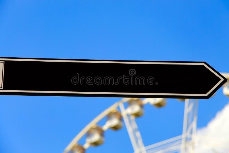 Segnale stradale nero in bianco o segnale stradale vuoto, direzione di rappresentazione, un cielo blu fotografia stock