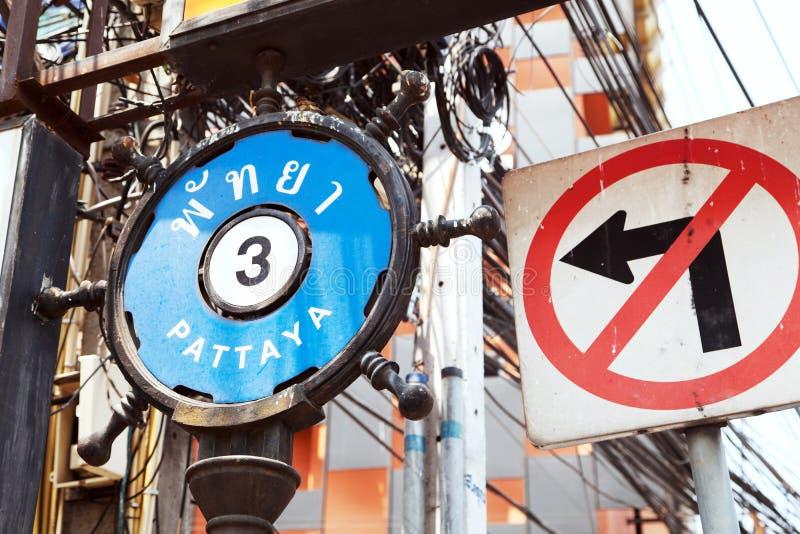 Segnale stradale PATTAYA 3 in inglese e tailandese accanto ad una NESSUNA SVOLTA A SINISTRA immagine stock