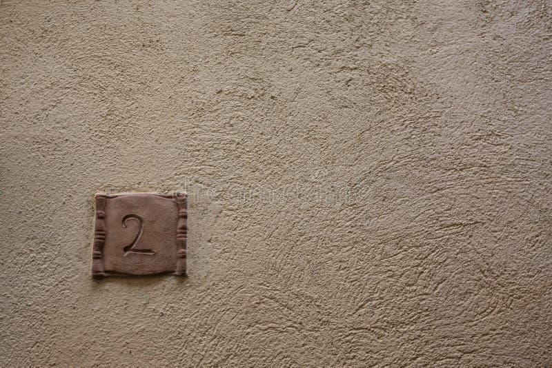 Segnale stradale su una casa che legge il numero due fatto da ceramico marrone fotografie stock libere da diritti