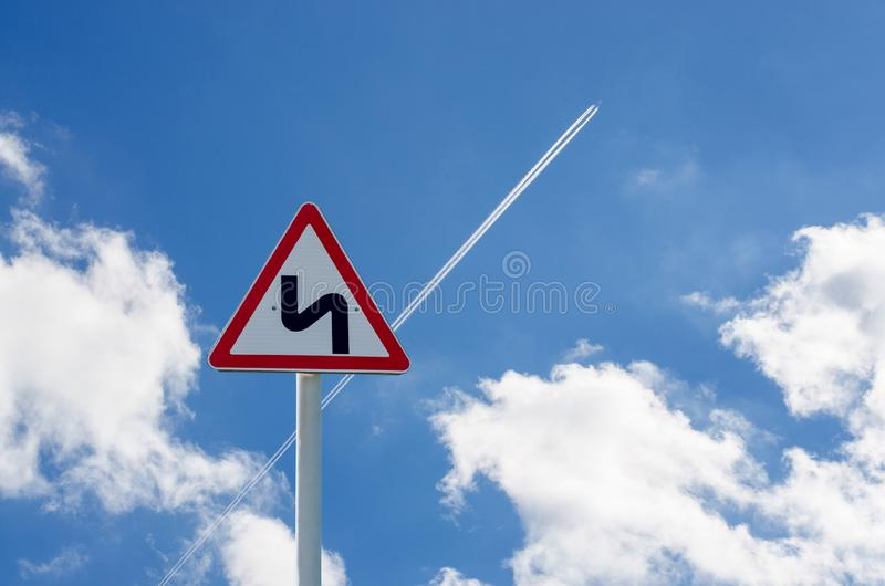 Segnale stradale sul fondo del cielo La traccia dell'aereo fotografia stock libera da diritti