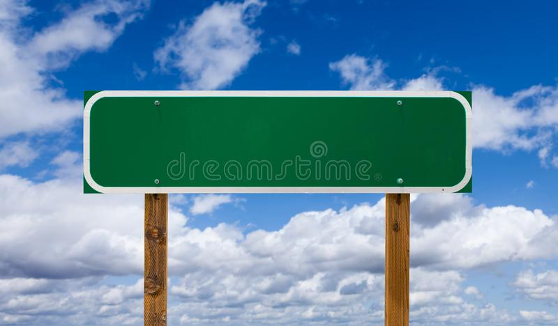 Segnale stradale verde in bianco con le poste di legno sopra cielo blu e le nuvole fotografie stock libere da diritti