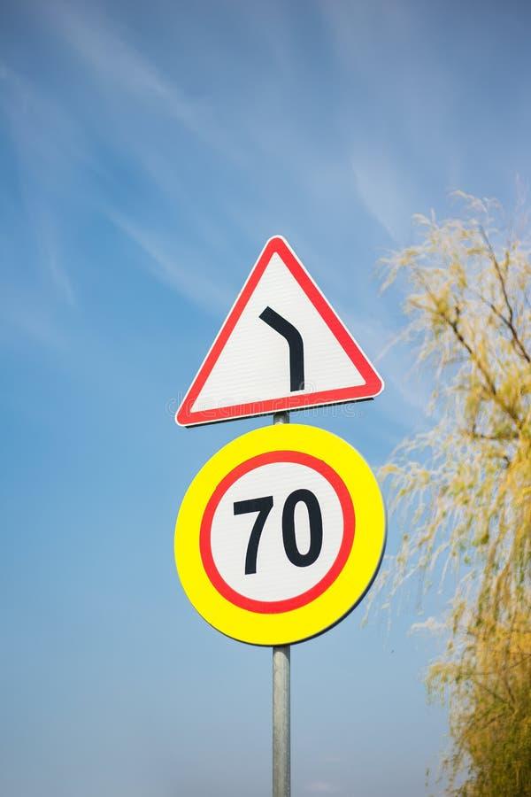 Segnali stradali differenti sui precedenti di cielo blu e di un albero immagine stock libera da diritti