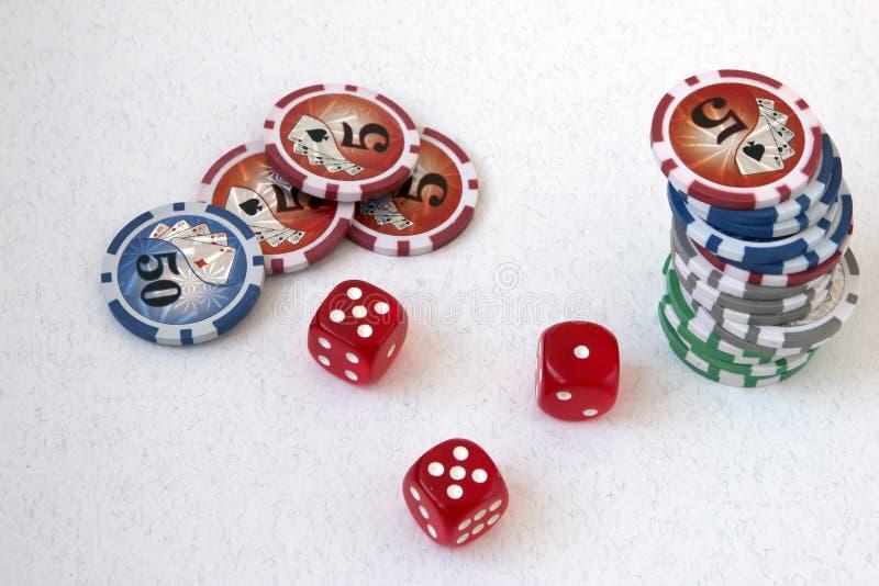 Segni, chip di poker e cubi di gioco, su un fondo bianco, con il numero cinque e un'unità fotografia stock libera da diritti