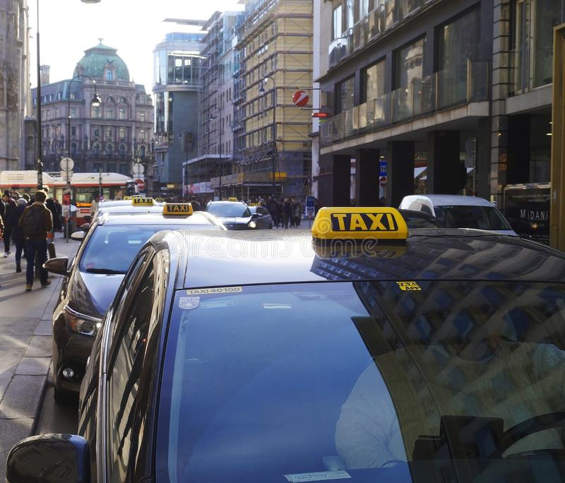 Segni del taxi sulle automobili parcheggiate nel centro di Vienna fotografia stock libera da diritti