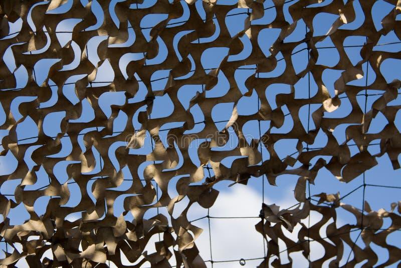 segni di guerra Dettaglio di una carta beige di griglia del cammuffamento, sul cielo blu inferiore immagine stock