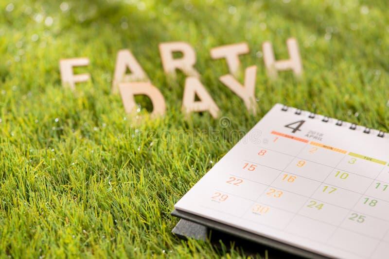 Segni il concetto con lettere felice del giorno di terra con il calendario su erba verde immagine stock