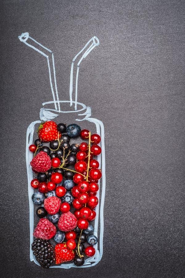 Segni la bottiglia col gesso dipinta con le varie bacche fresche per il frullato o il succo sul fondo scuro della lavagna fotografia stock