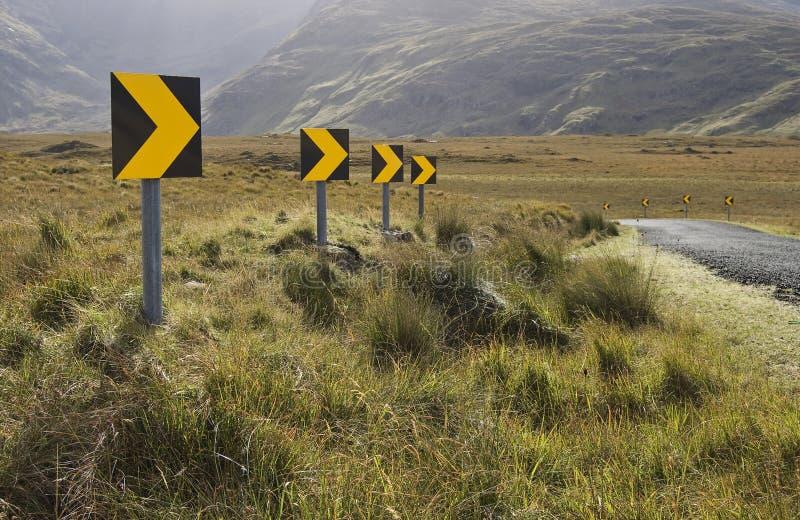 Segni pericolosi della curva stradale immagini stock