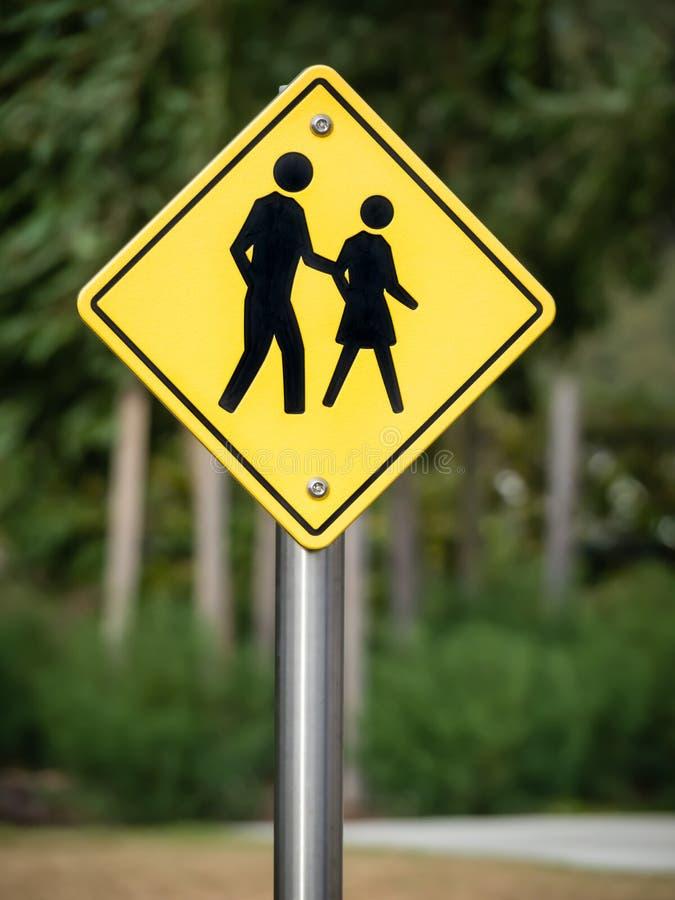 Segno al passaggio pedonale con la camminata della gente immagini stock