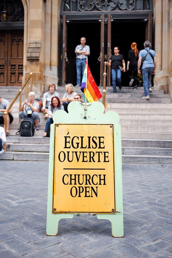 Segno aperto di una chiesa d'affermazione gay con una bandiera di orgoglio dell'arcobaleno del lgbt su ed il gruppo di persone ch fotografia stock libera da diritti