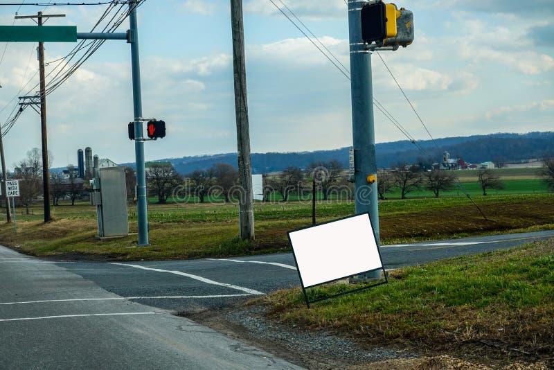 Segno bianco accanto a una strada di campagna vicino a un incrocio fotografia stock libera da diritti