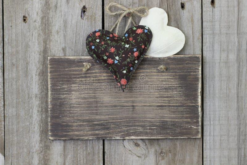Segno in bianco che appende sulla porta di legno con i cuori della mussola e del calicò immagini stock