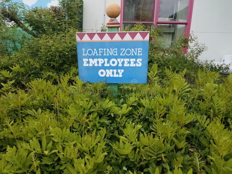 Segno degli impiegati di zona di Loafing solo e piante verdi fotografie stock