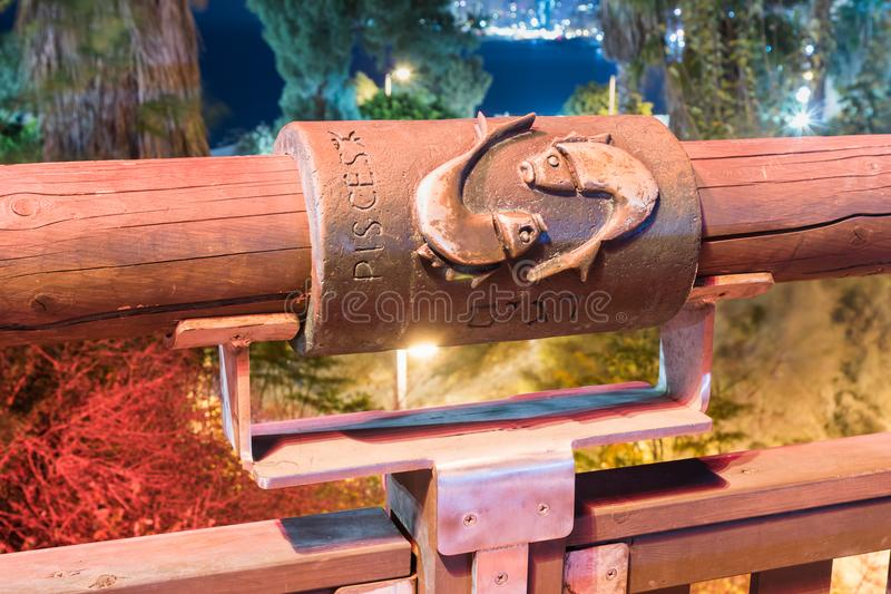 Segno dei pesci dello zodiaco sul ponte del ponte di desiderio alla luce thered di un riflettore situato sulla vecchia città Yafo fotografia stock libera da diritti