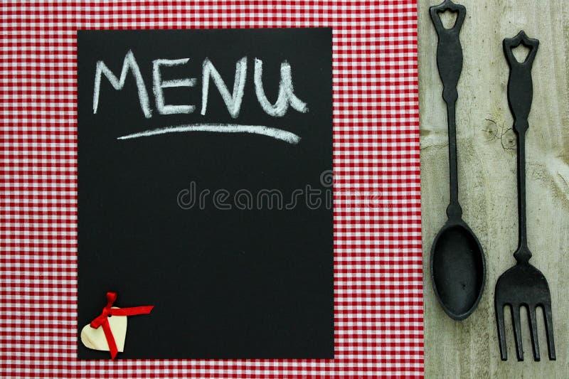 Segno del menu della lavagna sulla tovaglia a quadretti rossa con il cucchiaio e la forchetta del ghisa fotografia stock