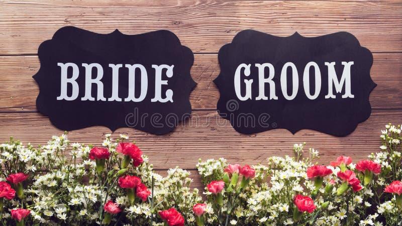 Segno del testo dello sposo e della sposa su fondo di legno decorato con il fiore, stile d'annata concetto del segno di nozze fotografie stock