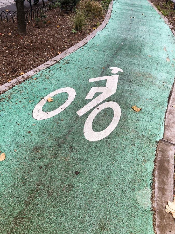 Segno del vicolo della bici su una strada verde fotografia stock