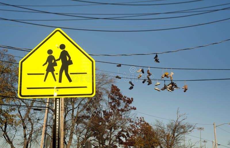 Segno dell'incrocio di scuola con le scarpe da tennis che appendono sui cavi di telefono immagini stock