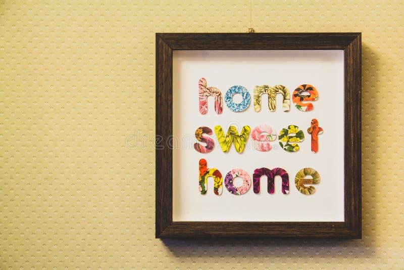 Segno della casa dolce casa appeso su una parete immagine stock libera da diritti