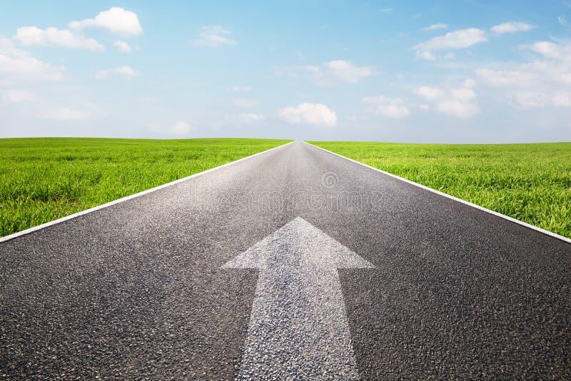 Segno della freccia che indica in avanti sulla strada diritta lungamente vuota fotografia stock