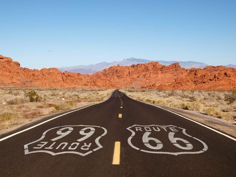 Segno della pavimentazione dell'itinerario 66 con le montagne rosse della roccia fotografie stock libere da diritti