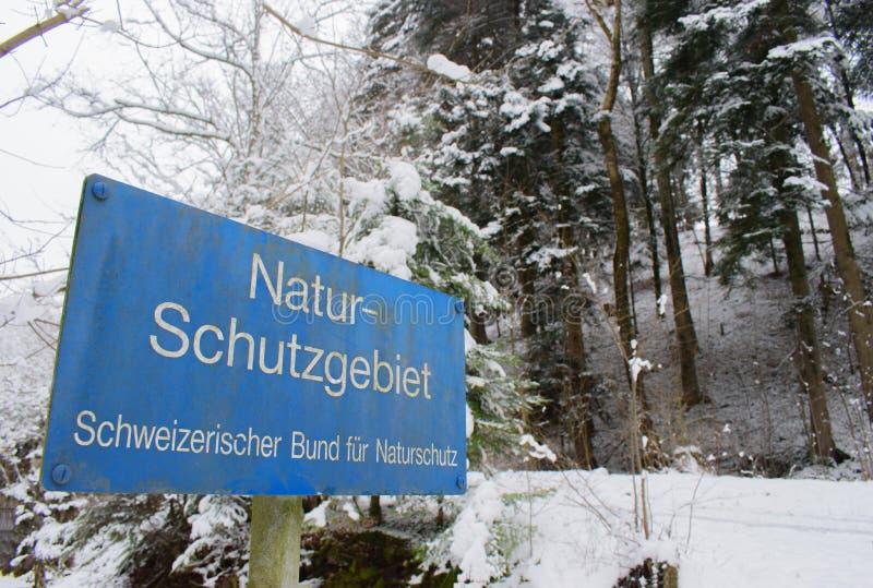 Segno della riserva naturale e neve fresca in una foresta con gli alberi alti in Svizzera immagini stock