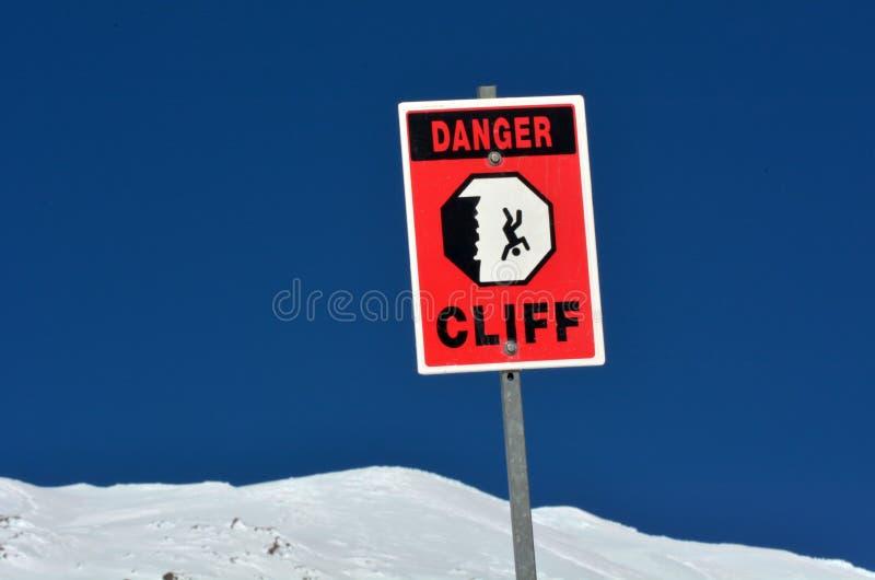 Segno della scogliera ripida del pericolo sulla sommità della montagna del capo della neve immagini stock libere da diritti