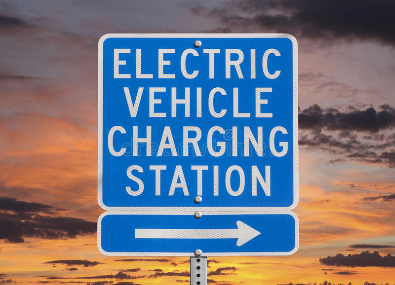 Segno della stazione di carico del veicolo elettrico con il cielo di tramonto immagine stock libera da diritti