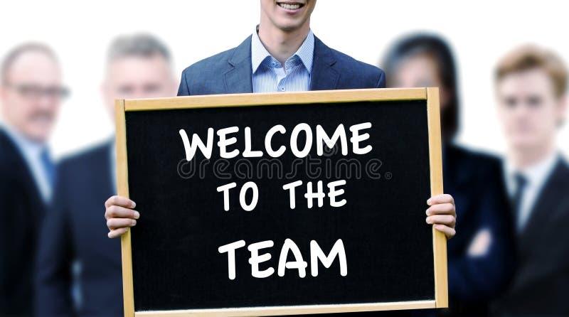 Segno della tenuta dell'uomo d'affari con il benvenuto di parole al gruppo immagini stock