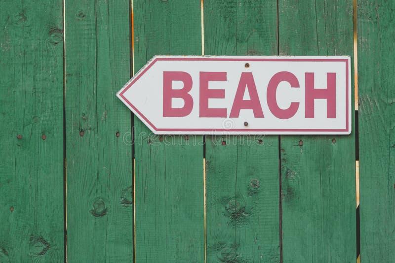 Segno di accesso della spiaggia sul recinto di legno verde rustico immagine stock