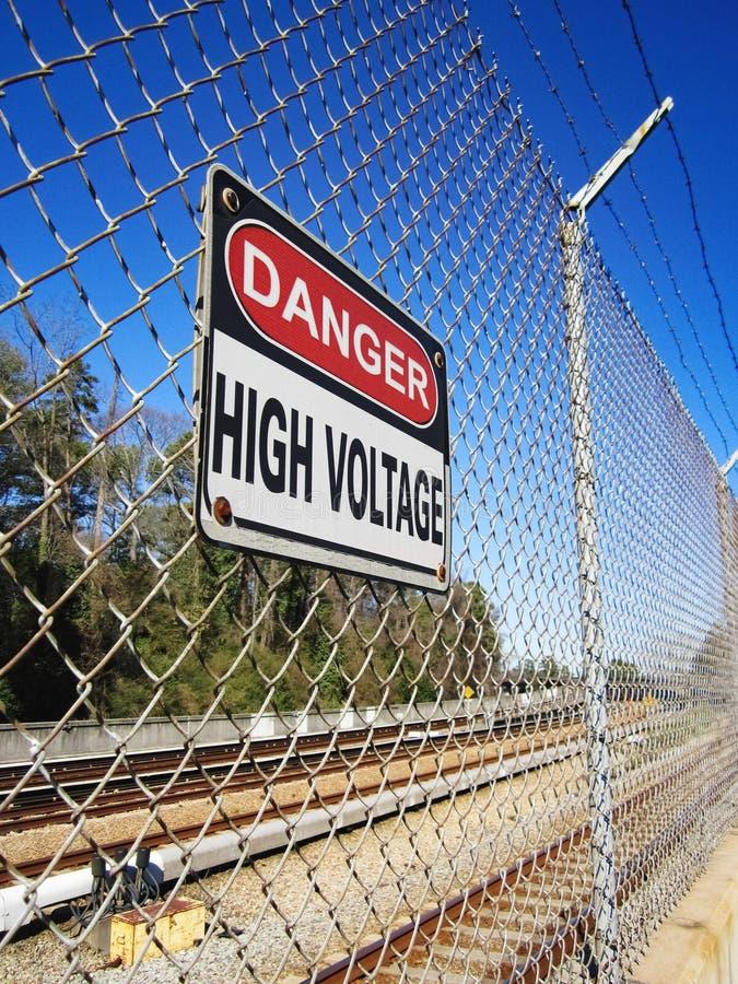 Segno di alta tensione pericoloso lungo la ferrovia elettrica fotografia stock